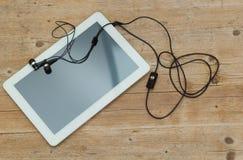 Comprimé et écouteurs de Digital sur le fond en bois Image libre de droits