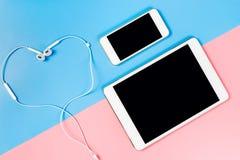 Comprimé et écran vides de téléphone avec le coeur pour la musique d'amour Photos stock