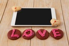 Comprimé et biscuits de Digital avec le message d'amour sur la surface en bois Photo libre de droits