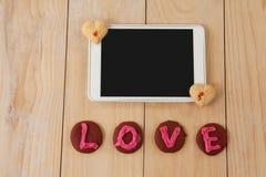 Comprimé et biscuits de Digital avec le message d'amour sur la surface en bois Photos stock