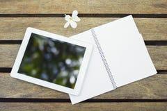 Comprimé et carnet numériques vides sur une table en bois Images stock