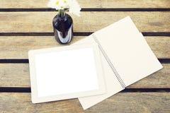 Comprimé et carnet numériques vides sur une table en bois dehors Photo stock