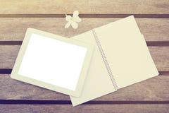 Comprimé et journal intime numériques vides sur une table en bois Photos stock