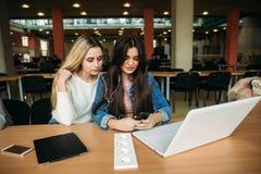 Comprimé et ordinateur portable d'utilisation d'étudiante deux dans la bibliothèque Et écoutent la musique Photographie stock libre de droits