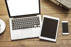 Comprimé et téléphone d'ordinateur portable sur l'espace de travail en bois Photos libres de droits