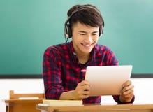 Comprimé heureux de lecture d'étudiant dans la salle de classe Image stock