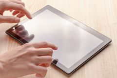 Comprimé noir dans des mains sur une table en bois image libre de droits