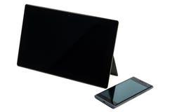 Comprimé noir moderne avec le téléphone portable d'isolement Photographie stock libre de droits