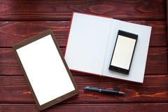 Comprimé numérique blanc sur la table en bois lumineuse Image libre de droits