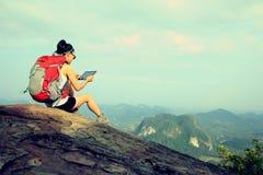 Comprimé numérique d'utilisation de randonneur de femme à la montagne images libres de droits