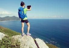 Comprimé numérique d'utilisation de randonneur sur le bord de falaise de montagne de bord de la mer Photos libres de droits