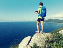 Comprimé numérique d'utilisation de randonneur sur le bord de falaise de montagne de bord de la mer Photographie stock