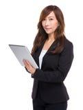 Comprimé numérique d'utilisation mûre de femme d'affaires Photographie stock