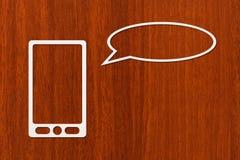 Comprimé ou smartphone de papier avec avec la bulle ou le ballon de la parole Image stock