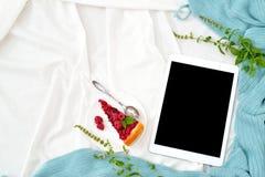 Comprimé plat, téléphone, tasse de café et fleurs de configuration sur la couverture blanche avec le plaid de turquoise Photos stock