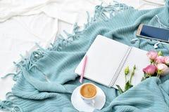 Comprimé plat, téléphone, tasse de café et fleurs de configuration sur la couverture blanche avec le plaid de turquoise Photographie stock libre de droits