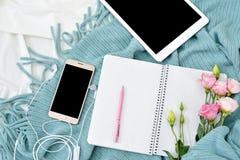 Comprimé plat, téléphone, tasse de café et fleurs de configuration sur la couverture blanche avec le plaid de turquoise Images stock