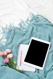 Comprimé plat, téléphone, tasse de café et fleurs de configuration sur la couverture blanche avec le plaid de turquoise Photo libre de droits