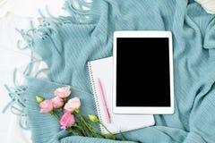 Comprimé plat, téléphone, tasse de café et fleurs de configuration sur la couverture blanche avec le plaid de turquoise Photo stock
