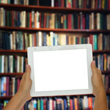 Comprimé vide avec des shelfs de bibliothèque à l'arrière-plan Images stock