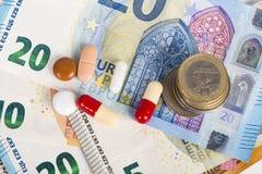 Comprimés blancs et rouges avec d'euro billets de banque et pièces de monnaie Photo libre de droits