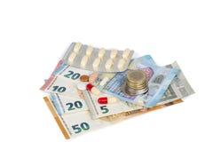 Comprimés blancs et rouges avec d'euro billets de banque et pièces de monnaie Image stock