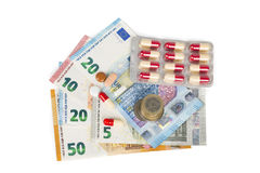 Comprimés blancs et rouges avec d'euro billets de banque et pièces de monnaie Image libre de droits