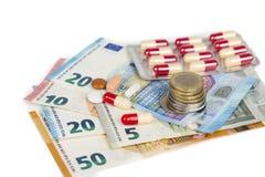 Comprimés blancs et rouges avec d'euro billets de banque et pièces de monnaie Photos stock