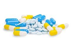 Comprimés de pilules bleues, jaunes et bleu-clair sur un CCB blanc d'isolement Images libres de droits