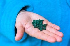 Comprimés de Spirulina dans la paume Photographie stock libre de droits