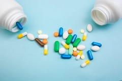 Comprimés et capsules multicolores, bouteille blanche pour les comprimés, pilules pharmaceutiques de médecine sur le fond bleu, u image stock