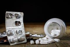Comprimés médicinaux sur une table en bois Pilules blanches dans le contai en plastique Photos stock