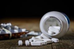 Comprimés médicinaux sur une table en bois Pilules blanches dans le contai en plastique Photos libres de droits