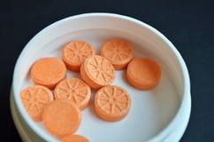 Comprimés ronds oranges sous forme de mensonge orange dans un pot blanc rond sur un fond noir, plan rapproché images libres de droits