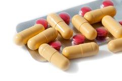 Comprimés rouges et jaunes et boursouflures dispersés sur un fond blanc images stock