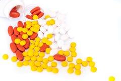 Comprimés rouges, jaunes, roses et bouteilles blanches de médecine photos stock