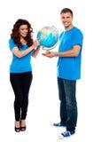Comprimento cheio de um globo da terra arrendada dos pares sobre o branco Fotografia de Stock