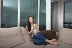 Comprimento completo da jovem mulher que olha a tevê na sala de visitas Imagem de Stock Royalty Free