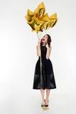 Comprimento completo da menina curiosa bonita que aponta em balões dourados Foto de Stock Royalty Free