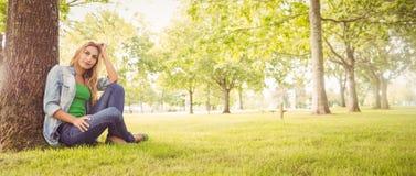 Comprimento completo da mulher de sorriso com mão no cabelo ao sentar-se sob a árvore fotos de stock royalty free