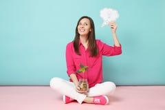 Comprimento completo da mulher na camisa cor-de-rosa, calças brancas que sentam-se em moedas de ouro da posse do assoalho no fras fotografia de stock royalty free