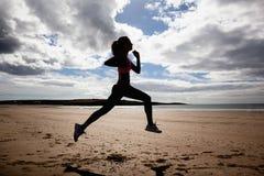 Comprimento completo da mulher saudável da silhueta que movimenta-se na praia imagens de stock