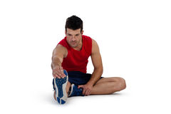Comprimento completo da pessoa de esportes que estica os pés ao exercitar fotos de stock