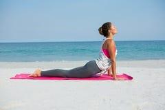 Comprimento completo da pose praticando da cobra da mulher na praia fotos de stock