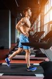 Comprimento completo da vista lateral do homem novo no sportswear que corre na escada rolante no gym fotografia de stock royalty free