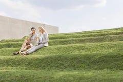 Comprimento completo das mulheres de negócios novas bonitas que usam o portátil ao se sentar na grama pisa contra o céu Fotos de Stock