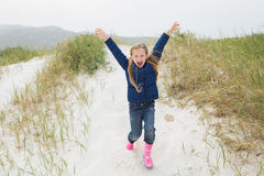 Comprimento completo de uma menina alegre que corre na praia Fotografia de Stock