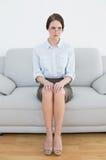 Comprimento completo de uma mulher bem vestido séria no sofá imagem de stock