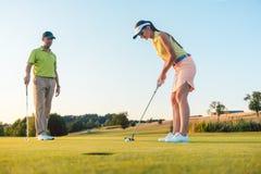 Comprimento completo de uma mulher que joga o golfe profissional com seu sócio masculino imagens de stock
