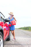 Comprimento completo do carro do reabastecimento da jovem mulher na estrada secundária Imagens de Stock